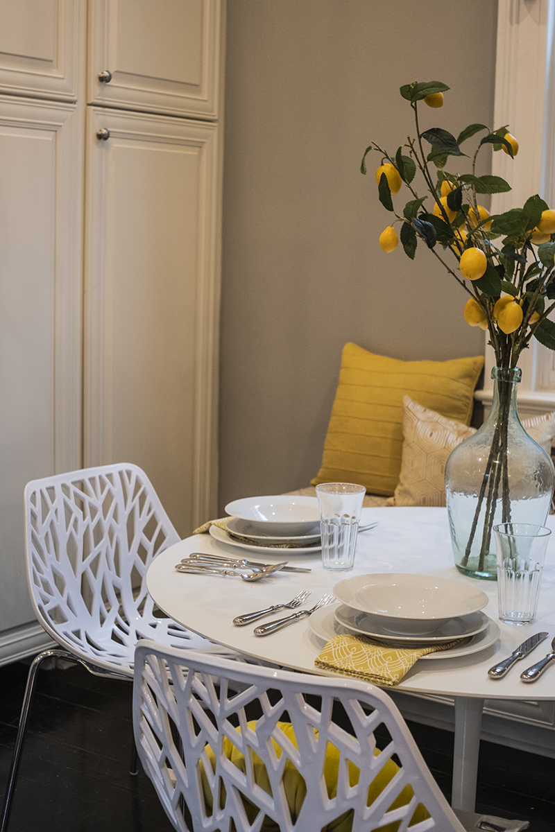 Bright and Cheery Breakfast Nook Closeup of white tulip table, white chairs, yellow throws, yellow napkins, lemon centerpiece